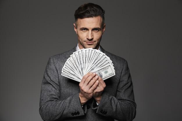 Foto van zelfverzekerde kerel 30s in pak met fan van geld dollarbiljetten en geïsoleerd over grijze muur