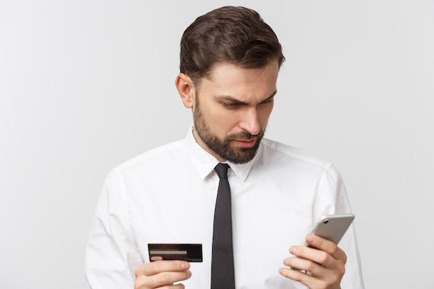 Foto van zelfverzekerde ondernemer man in pak en stropdas met smartphone en creditcard voor online betalen geïsoleerd over grijze ruimte
