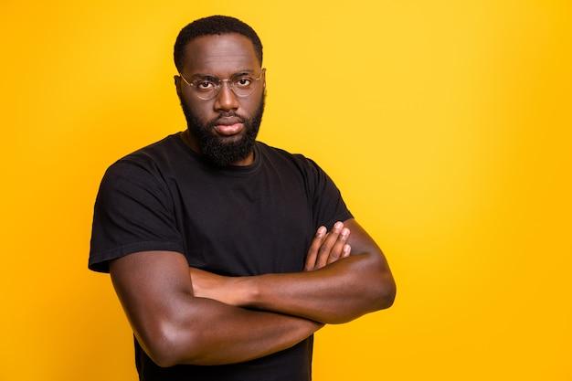 Foto van zelfverzekerde serieuze zwarte man die werkt als manager die openhartig naar je staart en naar je toespraak luistert voordat hij een baan accepteert in een t-shirt geïsoleerd met gevouwen handen levendige kleurenmuur
