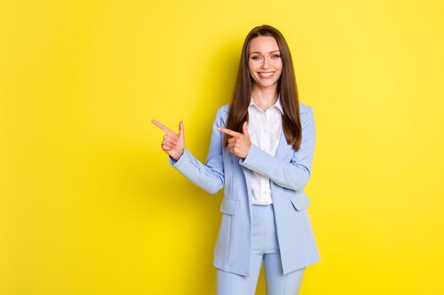 Foto van zelfverzekerde slimme econoom bankier meisje wijst wijsvinger display zakelijke partnerschap advertentie draag jas broek geïsoleerd over heldere glans kleur achtergrond