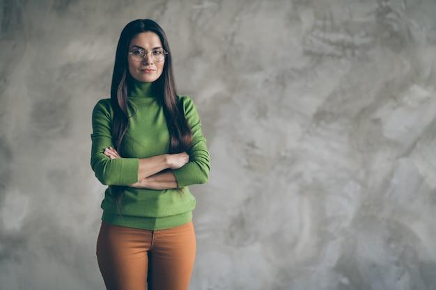Foto van zelfverzekerde strenge vrouw in oranje broek broek met gevouwen handen staande in de buurt van lege ruimte geïsoleerde grijze muur betonnen achtergrond kleur
