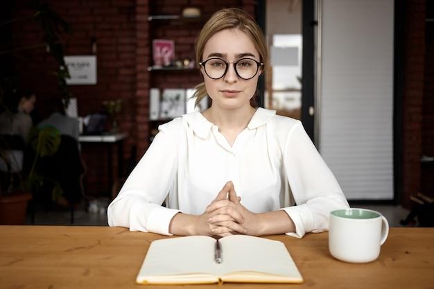 Foto van zelfverzekerde, vriendelijk ogende jonge vrouw hr-manager die een witte blouse en een bril draagt, zittend aan een bureau met de handen gevouwen tijdens het sollicitatiegesprek, vragen stellen en aandachtig luisteren