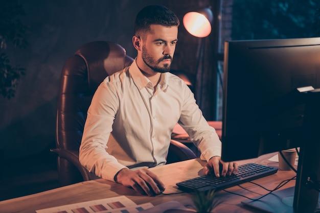 Foto van zelfverzekerde zakenman die bij de computer van het nachtploeggebruik werkt
