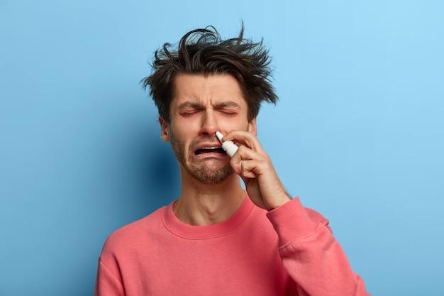 Foto van zieke man heeft verstopte neus, spuit met neusdruppels, heeft een ontevreden uitdrukking, verkouden, draagt een roze trui, poseert tegen blauwe muur, voelt zich onwel. mensen, gezondheidszorgconcept