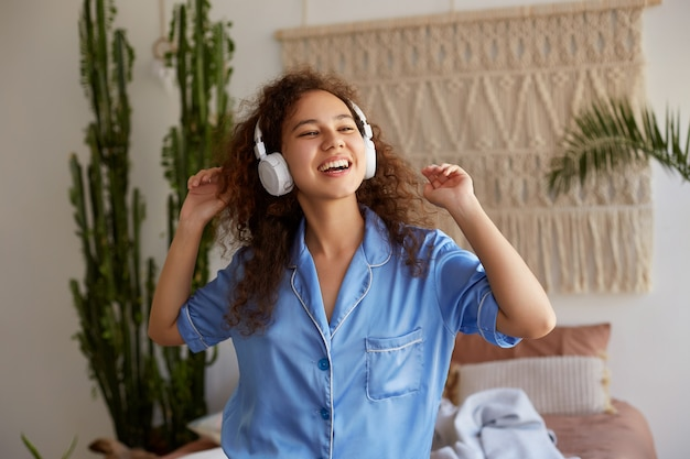 Foto van zingende krullende jonge mooie afro-amerikaanse dame, favoriete muziek in koptelefoon luisteren, kijkt weg en glimlachen.