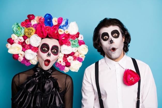 Foto van zombie spook paar man dame geschokt open mond sprakeloos ontdek zelf onderwereld draag zwarte jurk dood kostuum rozen hoofdband bretels geïsoleerde blauwe kleur achtergrond