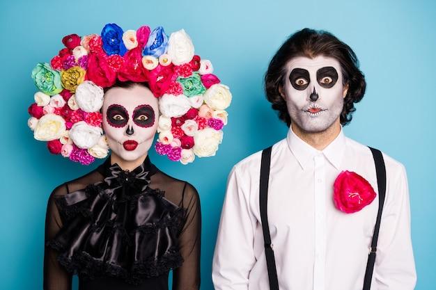 Foto van zombie spookachtig paar man dame maken grimas eng staren angstaanjagende kinderen oktober evenement dragen zwarte jurk dood kostuum rozen hoofdband bretels geïsoleerde blauwe kleur achtergrond