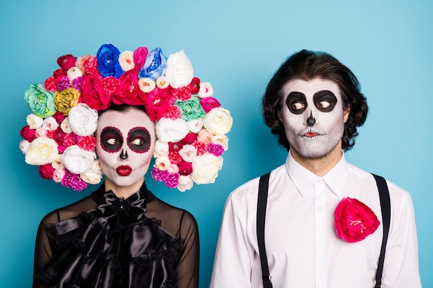Foto van zombie spookachtig schepsel paar man dame enge blik verward wakker begraafplaats oud graf dragen zwarte jurk dood kostuum rozen hoofdband bretels geïsoleerde blauwe kleur achtergrond