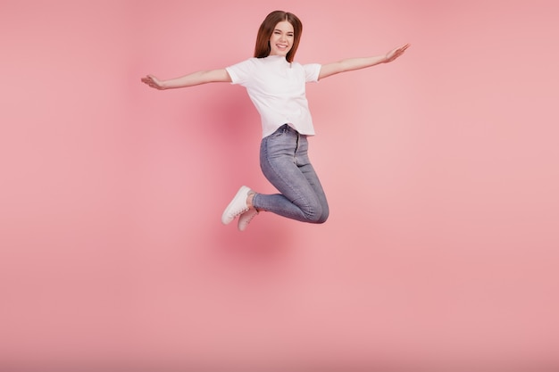 Foto van zorgeloos meisje springen hoog handen vleugels vliegtuig pose op roze achtergrond