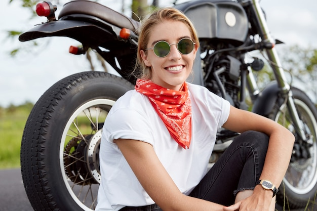 Foto van zorgeloze professionele jonge vrouwelijke motorrijder draagt trendy zonnebril en bandana, zit in de buurt van snelle zwarte motor, geniet van buiten rijden, zit op asfalt in de buurt van haar favoriete vervoer