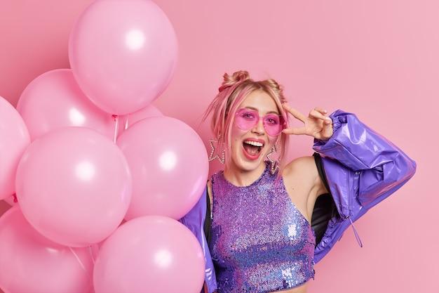 Foto van zorgeloze vrolijke vrouw heeft plezier op verjaardagsfeestje draagt trendy zonnebril en paarse jas roept uit van geluk maakt vredesgebaar houdt bos opgeblazen ballonnen houdingen over roze muur