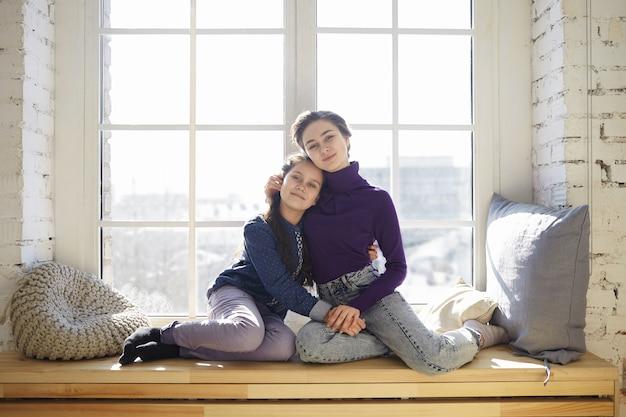 Foto van zorgzame gelukkige jonge moeder in casual kleding haar vrouwelijke kind zachtjes knuffelen terwijl u ontspant thuis, zowel zittend op de vensterbank en glimlachen