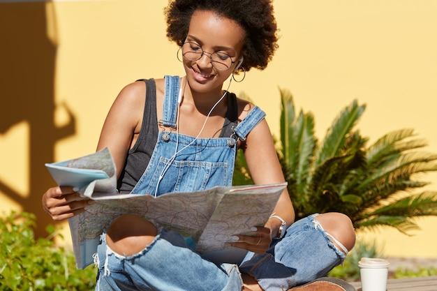 Foto van zwarte dame met knapperig haar gebruikt bestemmingskaart, zoekt interessante plaatsen om te bezoeken, houdt van bezienswaardigheden in onbekende stad, poseert in lotushouding tegen tropische planten, luistert graag naar muziek