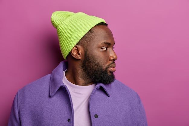 Foto van zwarte hipster man geconcentreerd opzij met doordachte uitdrukking, draagt groene hoed, paarse jas, denkt aan iets