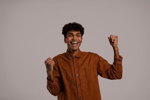 Foto van zwarte man danst en heeft plezier, lacht en ziet er gelukkig uit. man draagt shirt, geïsoleerde grijze kleur achtergrond.