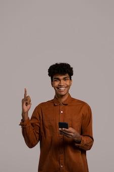 Foto van zwarte man houdt smartphones vast en wijst naar boven, ziet er goed uit. man draagt shirt, geïsoleerde grijze kleur achtergrond.