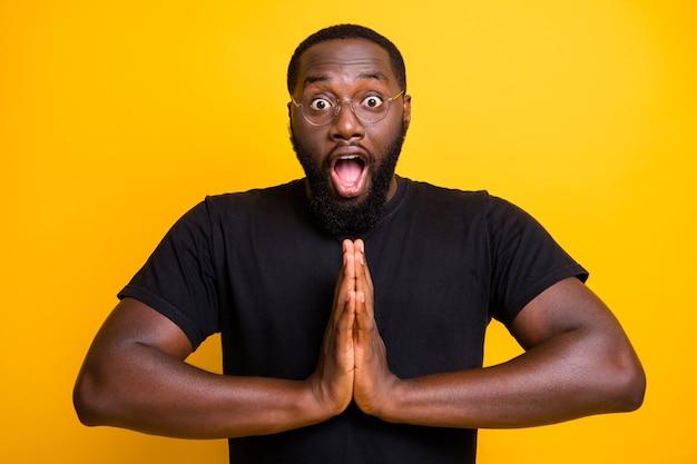 Foto van zwarte man in t-shirt bril brillen bril met handen gevouwen in gebed en verdoving op gezicht bedelen om goederen te kopen tijdens verkoop geïsoleerde levendige kleurenmuur
