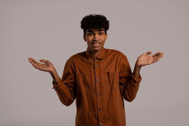 Foto van zwarte man ziet eruit alsof hij iets niet kent of vergeten is. man draagt shirt, geïsoleerde grijze kleur achtergrond.