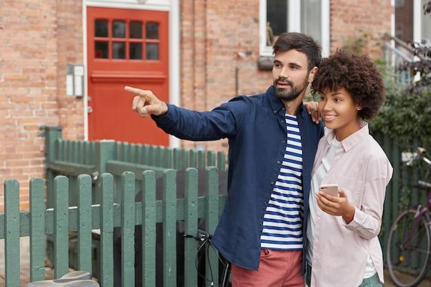 Foto van zwarte vrouw en blanke man lopen buiten, staan dicht