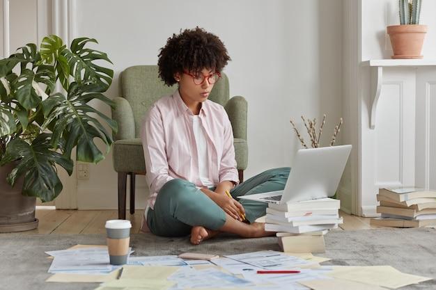 Foto van zwarte zakenvrouw gekleed in casual outfit, zit gekruiste benen met grafische diagrammen, analyseert bedrijfsinkomen