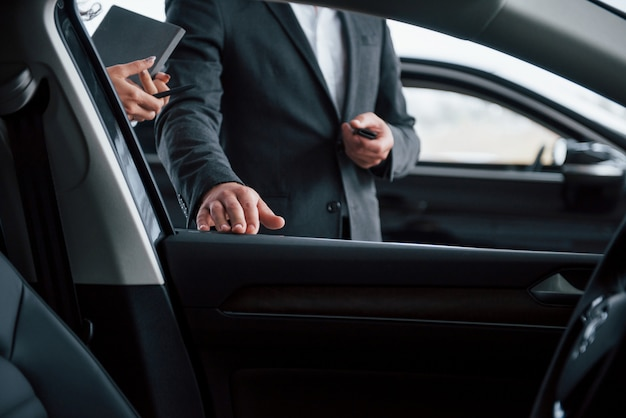 Foto vanaf de binnenkant van het voertuig. vrouwelijke klant en moderne stijlvolle bebaarde zakenman in de auto-salon