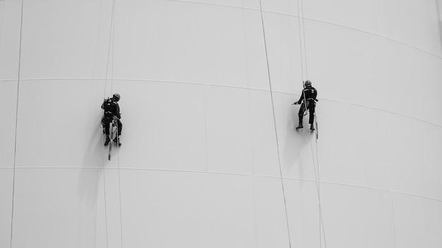 Foto zwart-wit man twee arbeiders controle touw naar beneden hoogte tank touw toegang inspectie van dikte schaal plaat opslagtank gas veiligheid werk op hoogte.