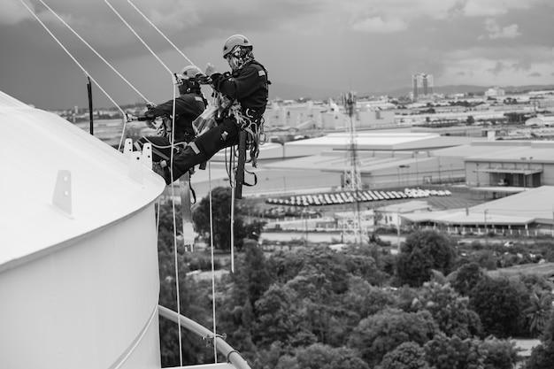 Foto zwart-wit man twee arbeiders controle touw naar beneden top dak hoogte tank touw toegang inspectie van dikte schaal plaat opslagtank gas veiligheid werk op hoogte.