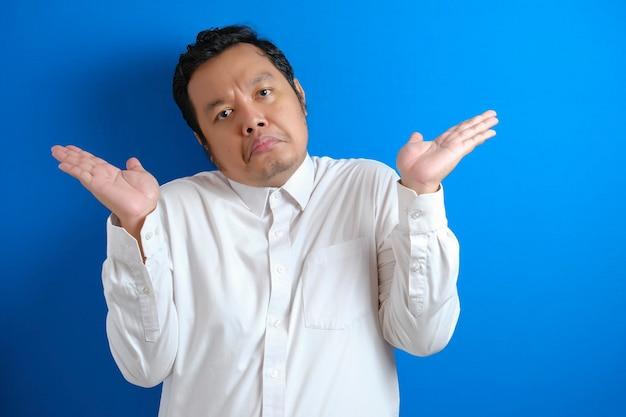 Fotobeeld van aziatische zakenman met schouderophalend gebaar, tonend ik weet het niet of afwijzing