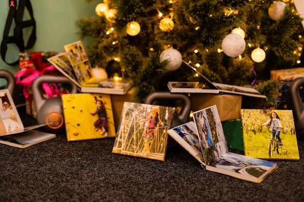Fotoboek, album en gewichten voor sporten bij de kerstboom als cadeauvakantie