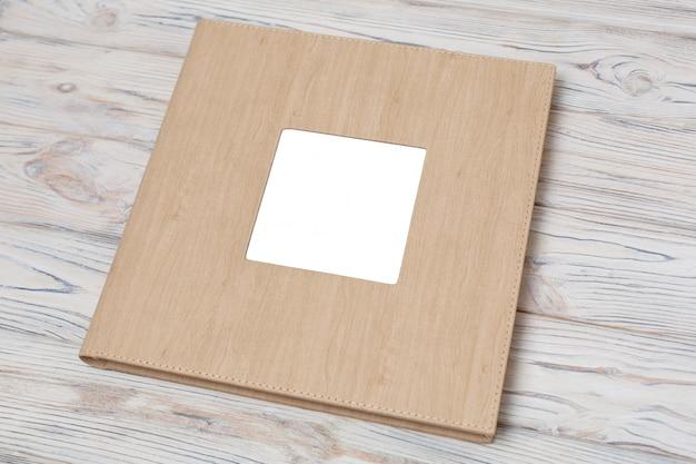Fotoboek met lederen omslag. het fotoalbum van het huwelijk met tussenvoegsel op een houten achtergrond.