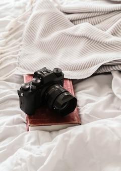 Fotocamera bovenop een boek op een bed