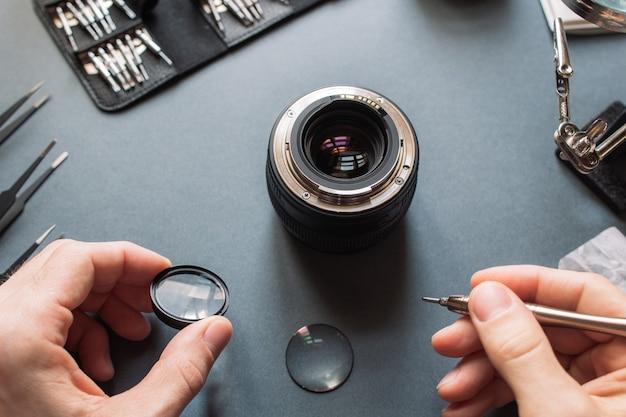 Fotocameralens repareren. technicus-ingenieur die optica controleert.