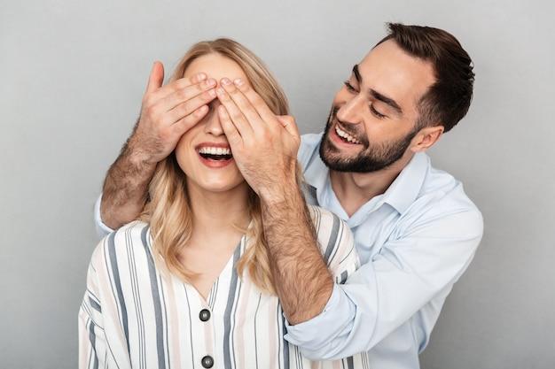 Fotoclose-up van een jonge man in casual kleding die lacht en de ogen van zijn vriendin bedekt, geïsoleerd over een grijze muur