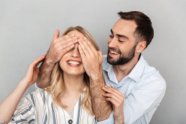Fotoclose-up van een knappe man in casual kleding die lacht en de ogen van zijn vriendin bedekt, geïsoleerd over een grijze muur