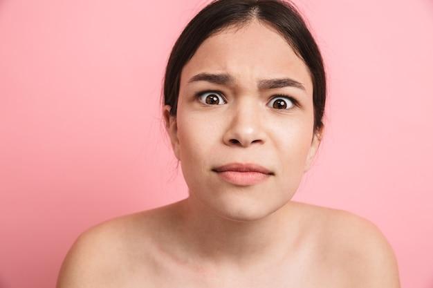 Fotoclose-up van europees shirtloos meisje met donker haar dat grimassen trekt en naar de voorkant kijkt geïsoleerd over roze muur