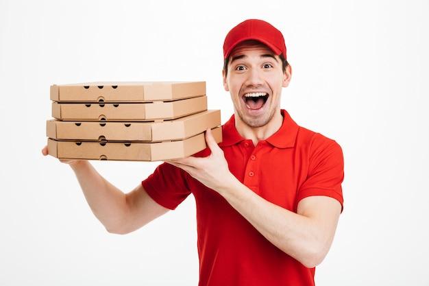 Fotoclose-up van knappe kerel van de leveringsdienst in rode t-shirt en glb-holdingsstapel pizzadozen, die over witte ruimte wordt geïsoleerd
