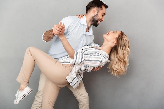 Fotoclose-up van romantisch paar in vrijetijdskleding glimlachend en dansend geïsoleerd over grijze muur