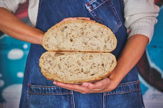 Fotodetail van vrouwelijke handen met een ambachtelijk brood dat in tweeën is gebroken met een blauw keukenschort.