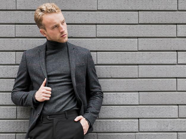 Fotogenieke jonge man in de buurt van een grijze muur