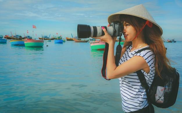 Fotograaf aziatische vrouw die foto's met camera professionele fotografie nemen in mui ne, visserijdorp met traditionele vietnamese boten, vietnam