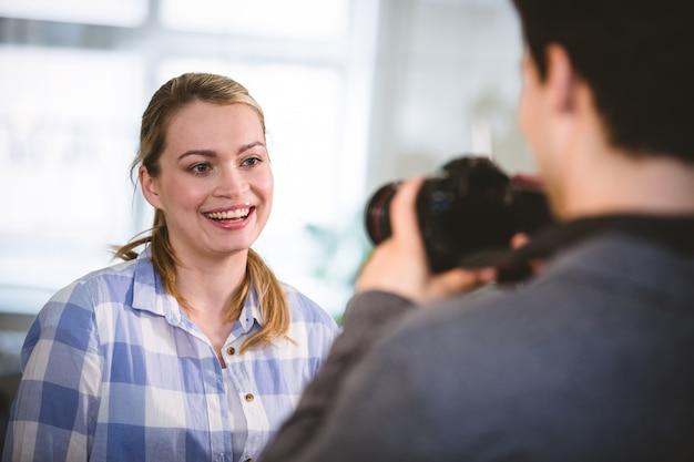 Fotograaf die beeld van gelukkige collega nemen op creatief kantoor