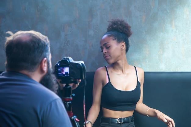 Fotograaf die een fotosessie doet met een jong zwart model dat op een bank zit