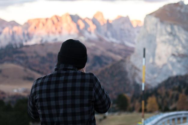 Fotograaf die naast de weg staat om zijn hoek te kijken om een foto te maken in bolzano, italië.