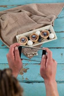 Fotograaf die op een afbeelding van een dessert klikt met een smartphone