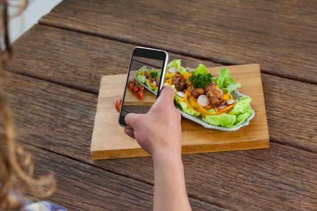Fotograaf die op een foto van eten klikt met een smartphone