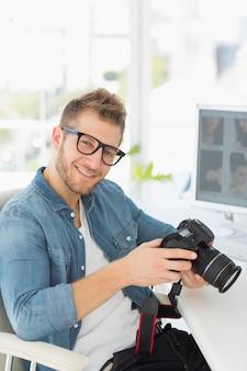 Fotograaf die zijn camera houdt en bij camera glimlacht