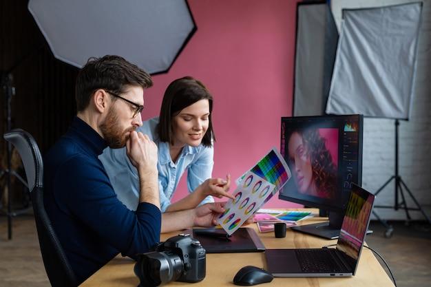 Fotograaf en grafisch ontwerper werken op kantoor met laptop, monitor, grafisch tekentablet en kleurenpalet.