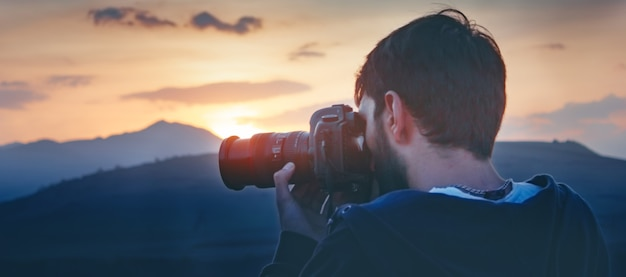 Fotograaf fotografeert de zonsondergang op de bergen
