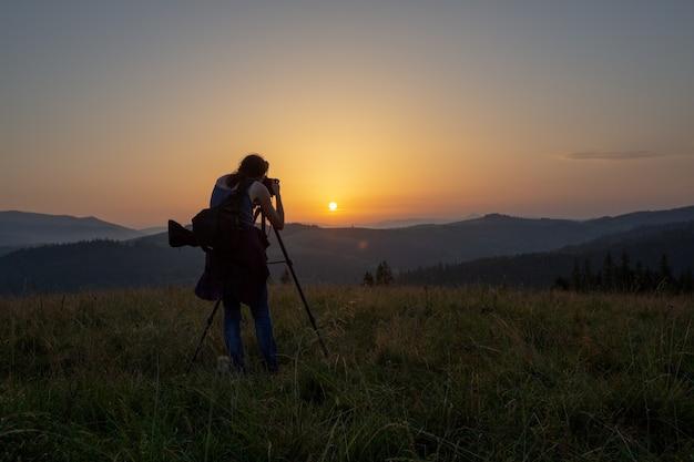 Fotograaf fotografeert landschap bij zonsondergang in de bergen