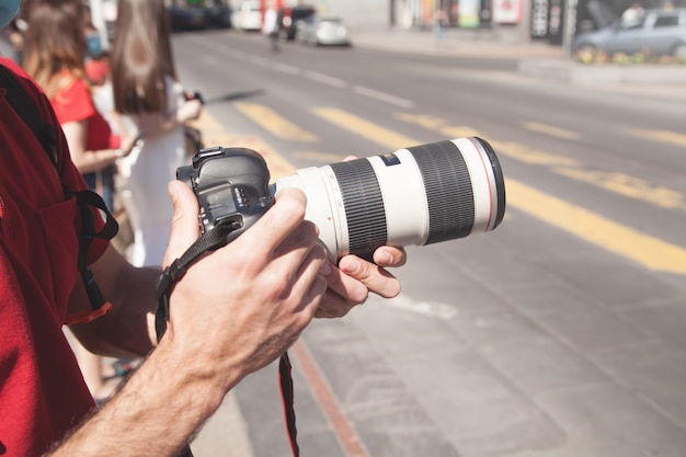 Fotograaf fotografeert met dslr-camera in een stad.